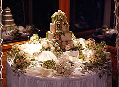 Wedding cake with peach and green flowers.