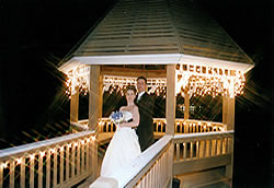 wedding couple in lit gazebo.