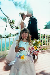 Flower girl in front of bride and groom kissing at their California wedding.