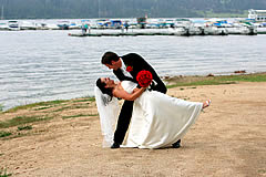 bride and groom on beach at lakefront wedding location.